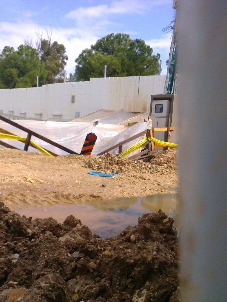 IAA excavation pit inside SWC construction site covered with plastic  tarp, supplied with dedicated electrical current for operating heavy  machinery and surrounded with warning tape