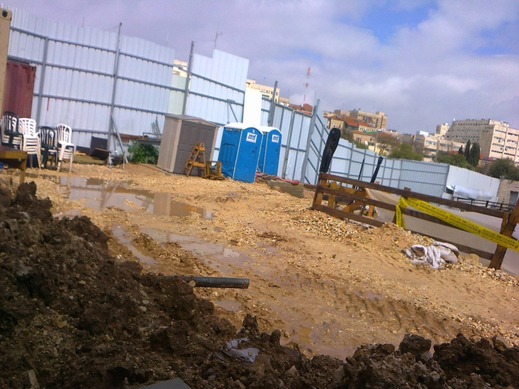 IAA excavation pit inside SWC construction showing inner enclosure wall and portable toilets rented for use by IAA teams onsite