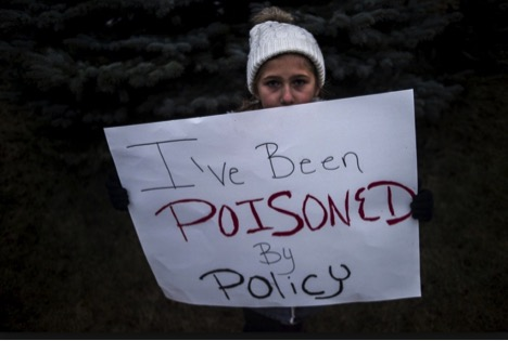 Person holding sign that reads I've been poisoned by policy