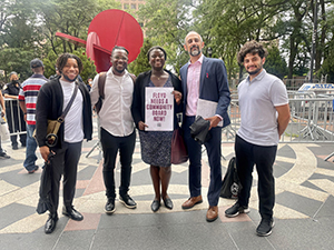 center for constitutional rights floyd team and plaintiffs stand outside the courthouse in a row holding a small sign, the text is not legible