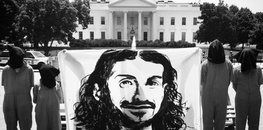 Protesters hold a banner image of Guantanamo prisoner Tariq Ba Odah outside the White House