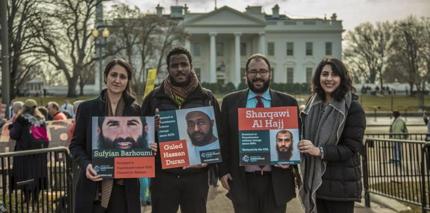 CCR Guantanamo team stands with photos of their clients in front of the White House