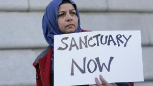 "woman holding a sign that reads ""Sanctuary Now"""