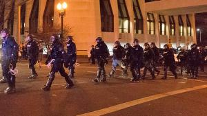 officers in riot gear marching