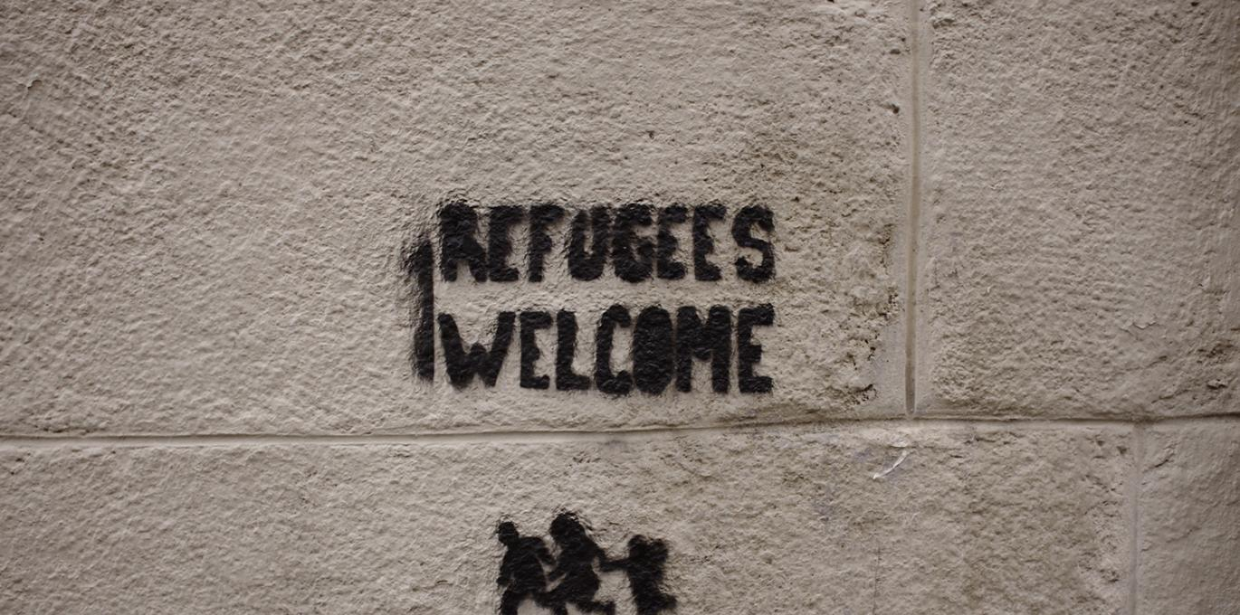 'Refugees Welcome' graffiti on cinder block wall