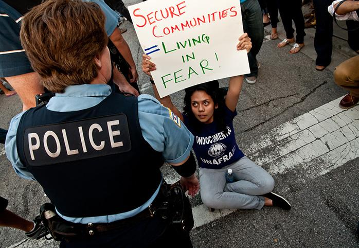 A protester holds up a sign while sitting on the ground, as a police offer stands over.