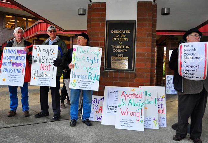 Protestors hold signs in support of the Olympia Food Coop's right to boycott Israeli products