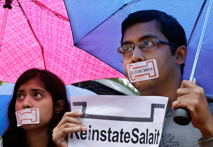 "Students with their mouths taped shut holding a sign that reads ""Reinstate Salaita"""