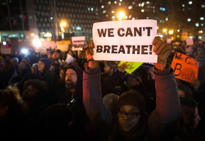 "Woman at a protest holds a sign that says ""We Can't Breathe!"""