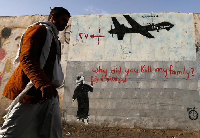 "Man walks past wall with graffiti of a U.S. drone and a small boy writing ""why did you kill my family?"""