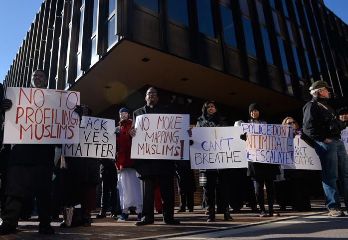 Demonstrators hold signs outside the courthouse