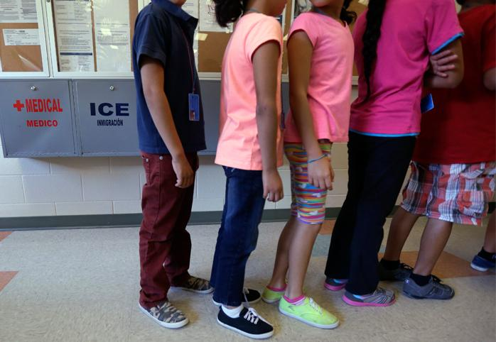 Children line up in the cafeteria at an immigration detention center in Texas.