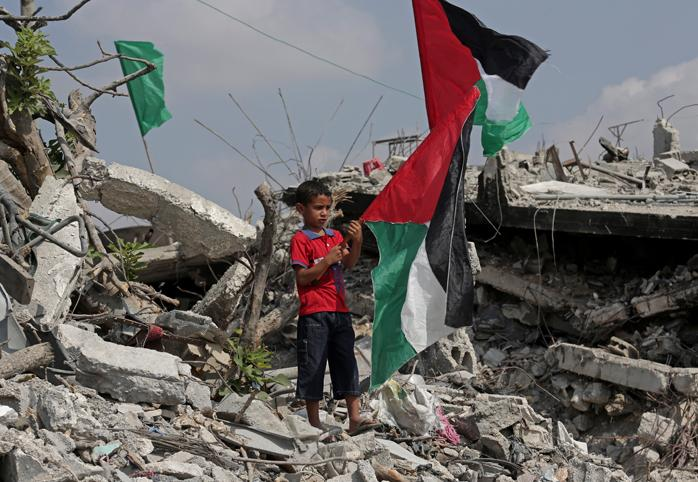 Young boy stands in rubble holding Palestinian flag