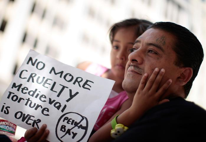 "A father and daughter at a protest holding a sign that reads ""NO MORE CRUELTY"""