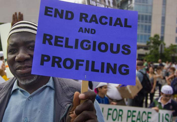 "Protestor holds a sign that says ""End Racial and Religious Profiling"""