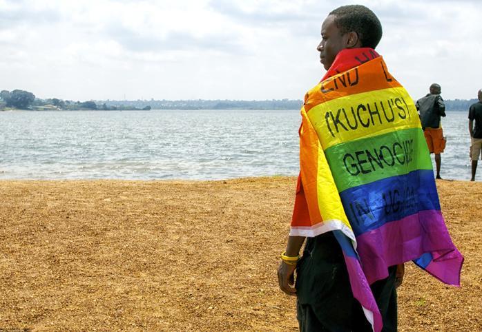 "Man wearing a rainbow flag that reads ""End LGBTI (Kuchu's) Genocide in Uganda"""